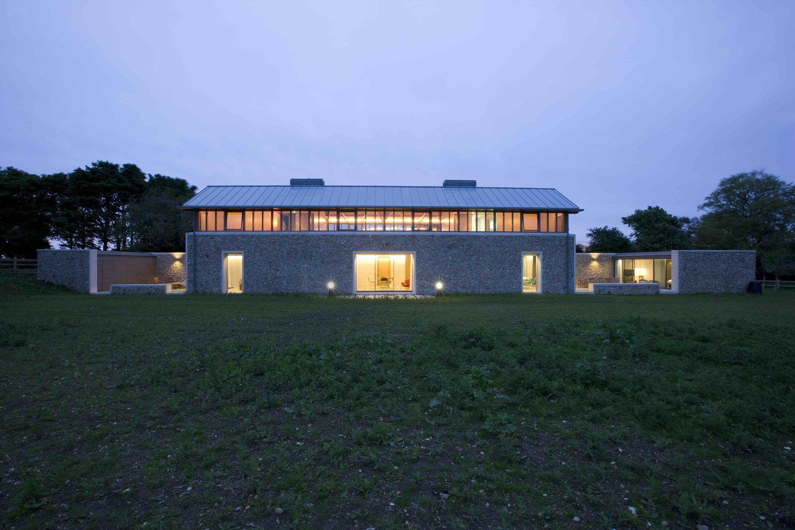 A home that feels like a refuge while still connecting its user to their surrounding environment, The Long House on the North coast of Norfolk has flint walls that pay homage to the barns and ancient churches in the area. Designed by British masters Sir Michael and Lady Patty Hopkins, this house melds elements from medieval architecture with distinctly modernist features.