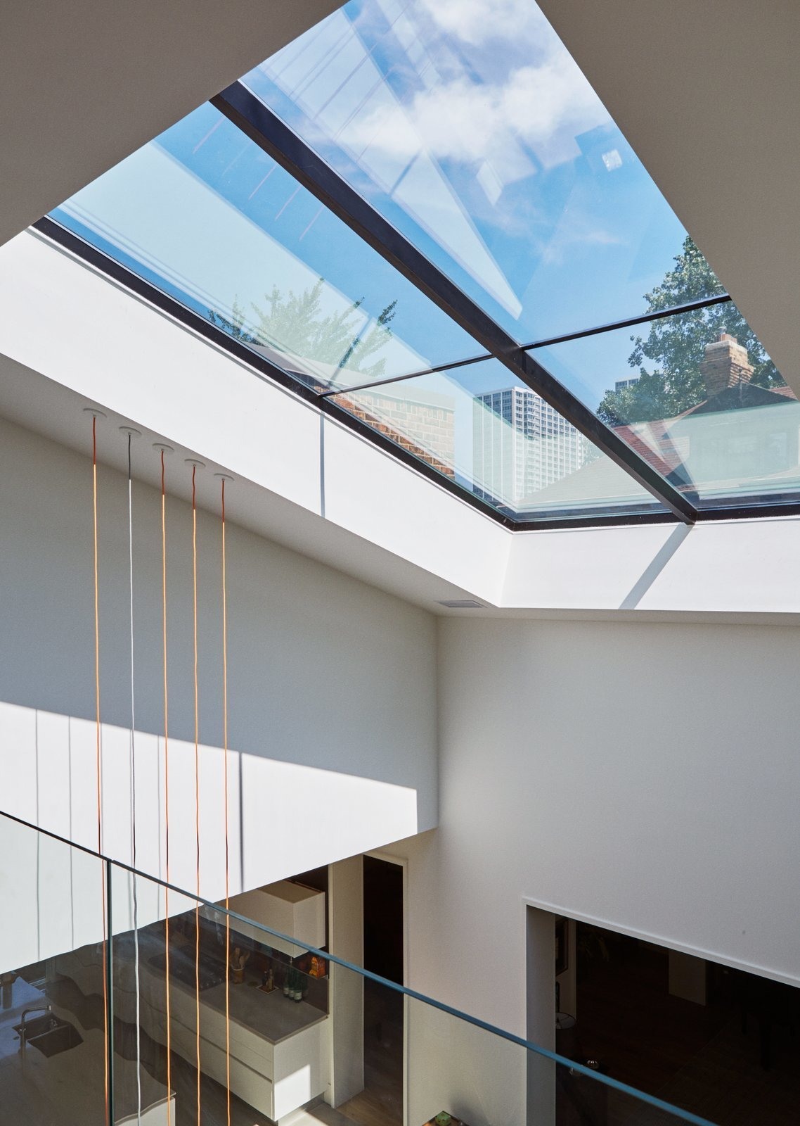 dSPACE Studio transformed a 1970s style Chicago residence into a bright, open and stylish home with an expansive 20-foot skylight that presents views of the surrounding neighborhood. Tagged: Windows, Skylight Window Type, and Metal.  Photo 5 of 10 in 10 Light-Filled Homes With Interesting Skylights