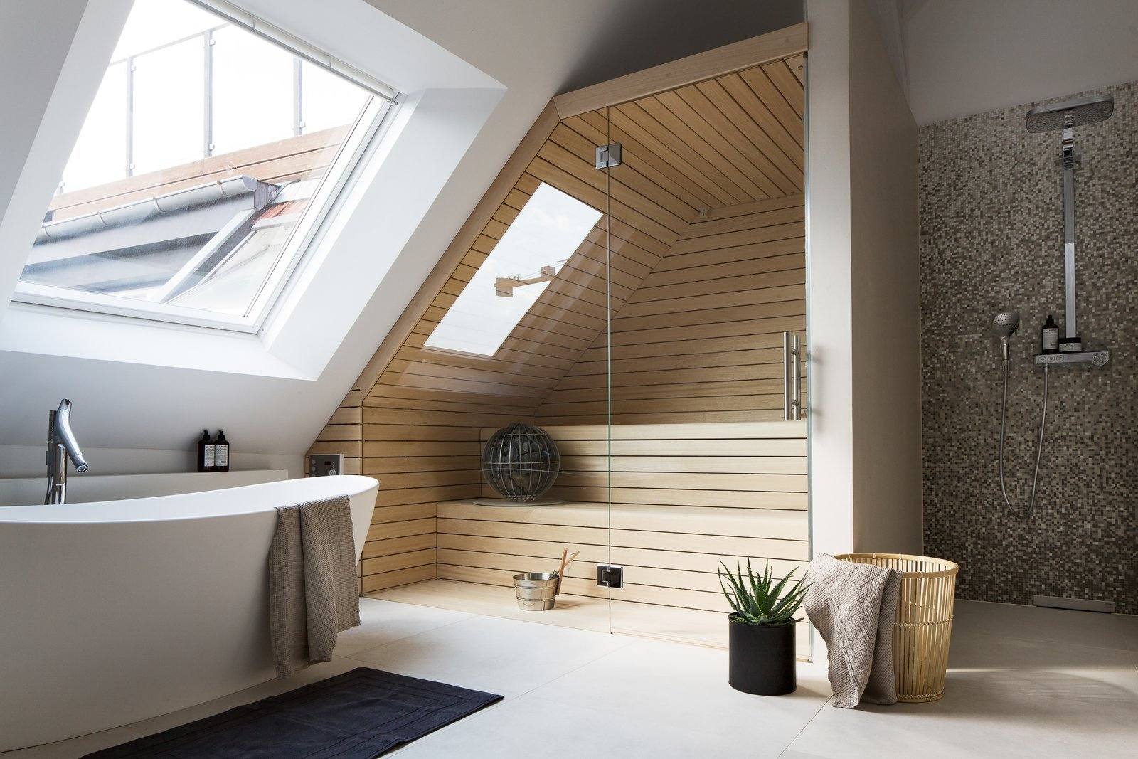 This converted attic in a turn-of-the-century building in Berlin's Charlottenburg neighborhood has a large skylight close the bathtub, on the side-slope of the roof, which allows one to look up at the sky while having a relaxing soak.