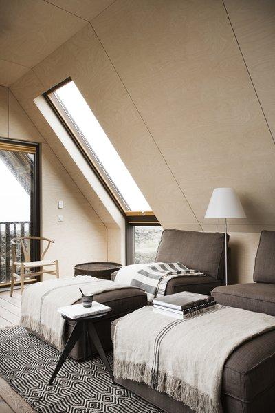 Modern home with living room, chair, floor lighting, and light hardwood floor. Photo 4 of Coastal Barn
