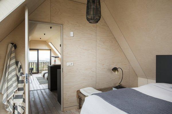 Modern home with bedroom, bench, table lighting, bed, and light hardwood floor. Photo 5 of Coastal Barn