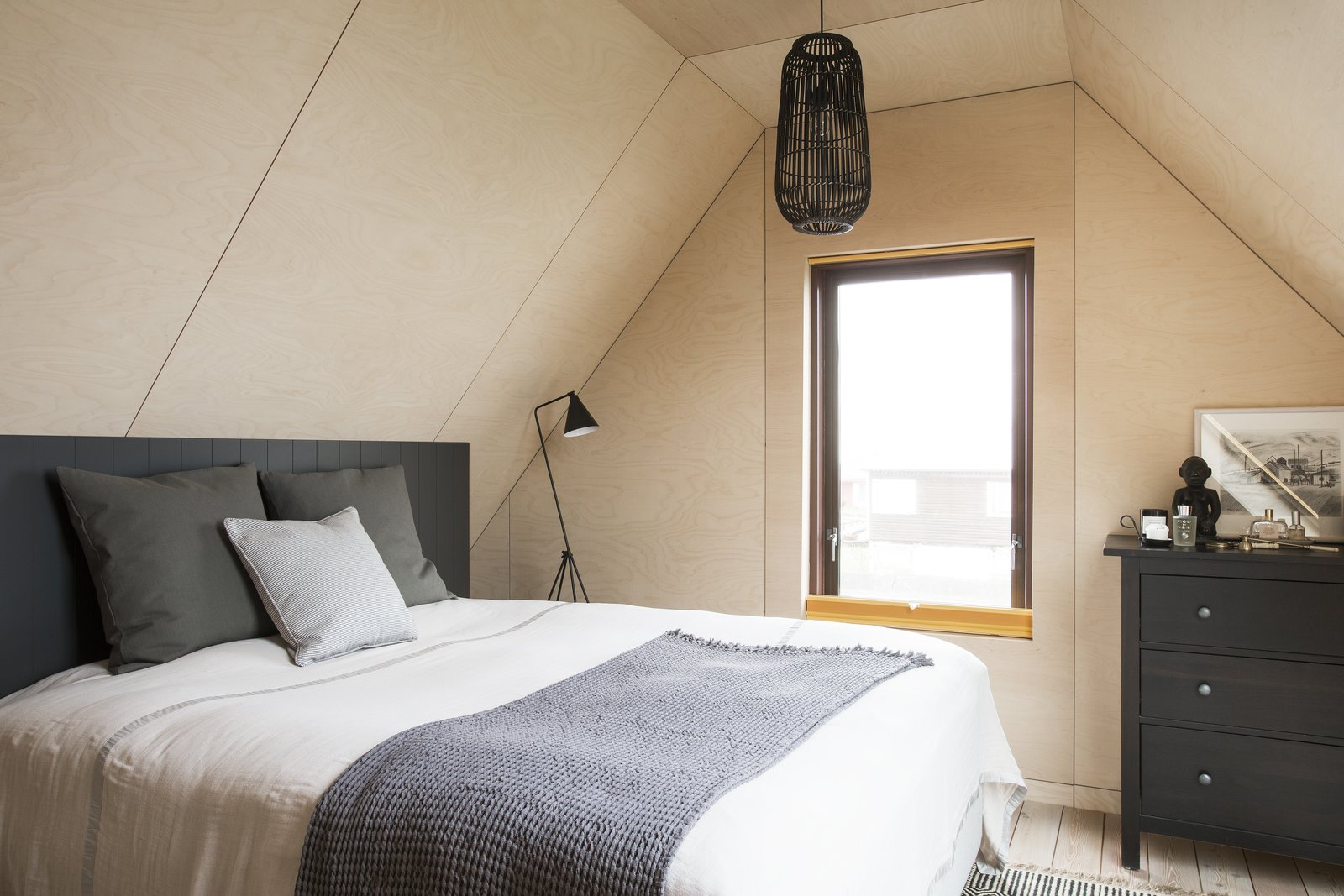 Tagged: Bedroom, Bed, Dresser, Ceiling Lighting, Light Hardwood Floor, and Floor Lighting.  Photo 6 of 12 in Get in Touch With Iceland's Rugged Landscape While Staying at This Modern Coastal Barn