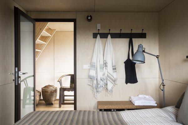 Modern home with bedroom, bench, storage, light hardwood floor, and floor lighting. Photo 7 of Coastal Barn
