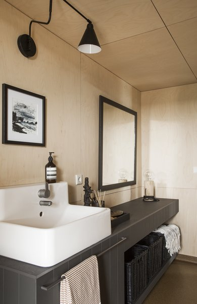 Modern home with bath room, tile counter, vessel sink, and wall lighting. Photo 9 of Coastal Barn