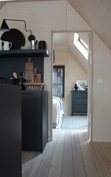 Modern home with bedroom, dresser, and light hardwood floor. Photo 11 of Coastal Barn