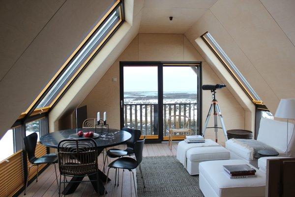 Modern home with dining room, table, chair, and light hardwood floor. Photo 3 of Coastal Barn