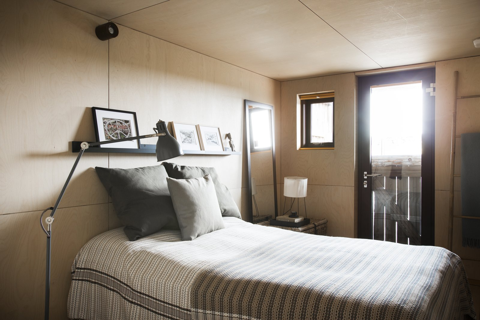 Tagged: Bedroom, Bed, Floor Lighting, Table Lighting, Night Stands, Light Hardwood Floor, Wall Lighting, and Shelves.  Photo 12 of 12 in Get in Touch With Iceland's Rugged Landscape While Staying at This Modern Coastal Barn