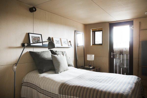 Modern home with bedroom, bed, floor lighting, and table lighting. Photo 12 of Coastal Barn