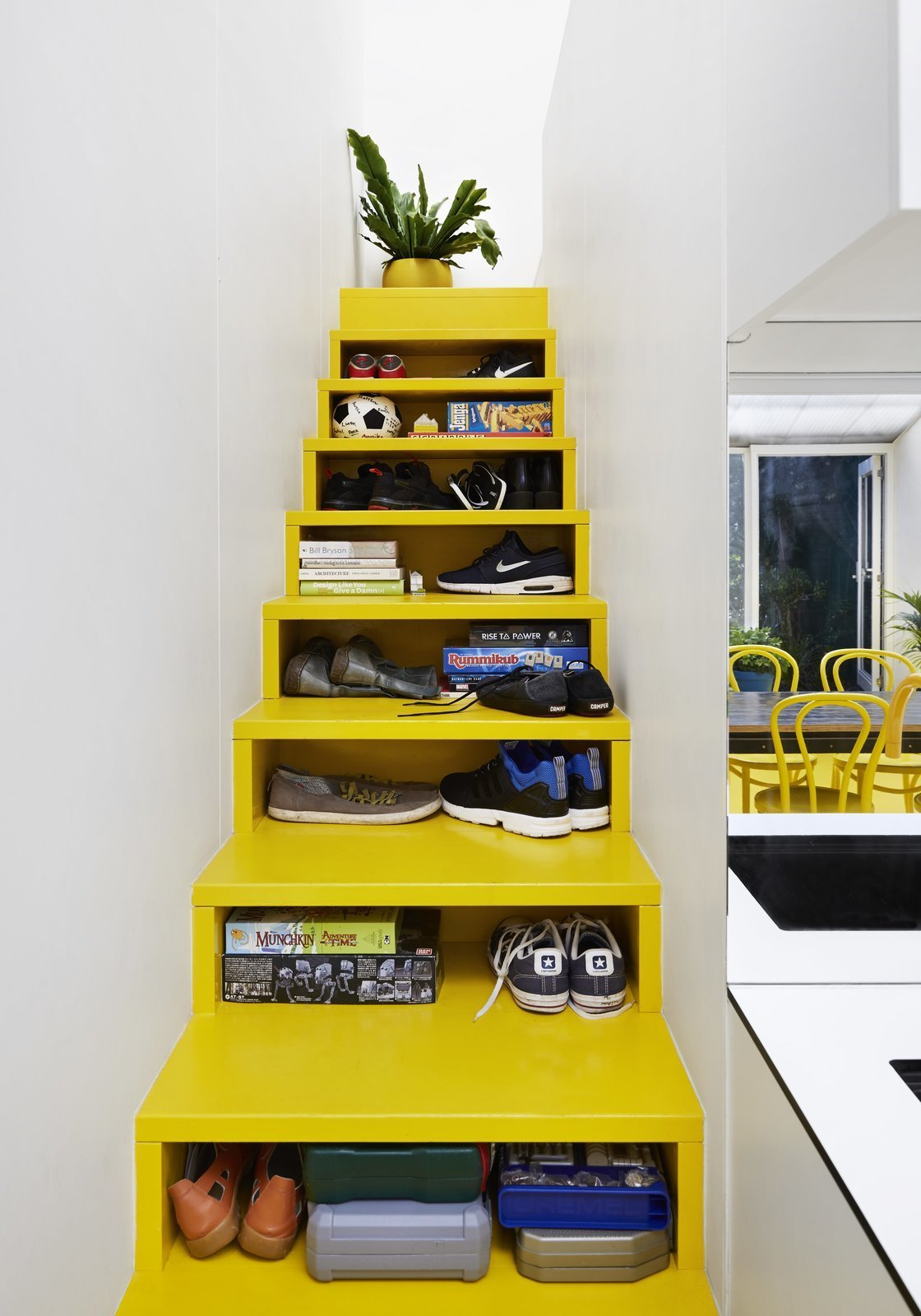 Architect Andrew Maynard's Melbourne home, which also doubles up as the office of his practice Austin Maynard Architects, includes a bright yellow staircase with opening slots in the front that serve as shelving and storage space.