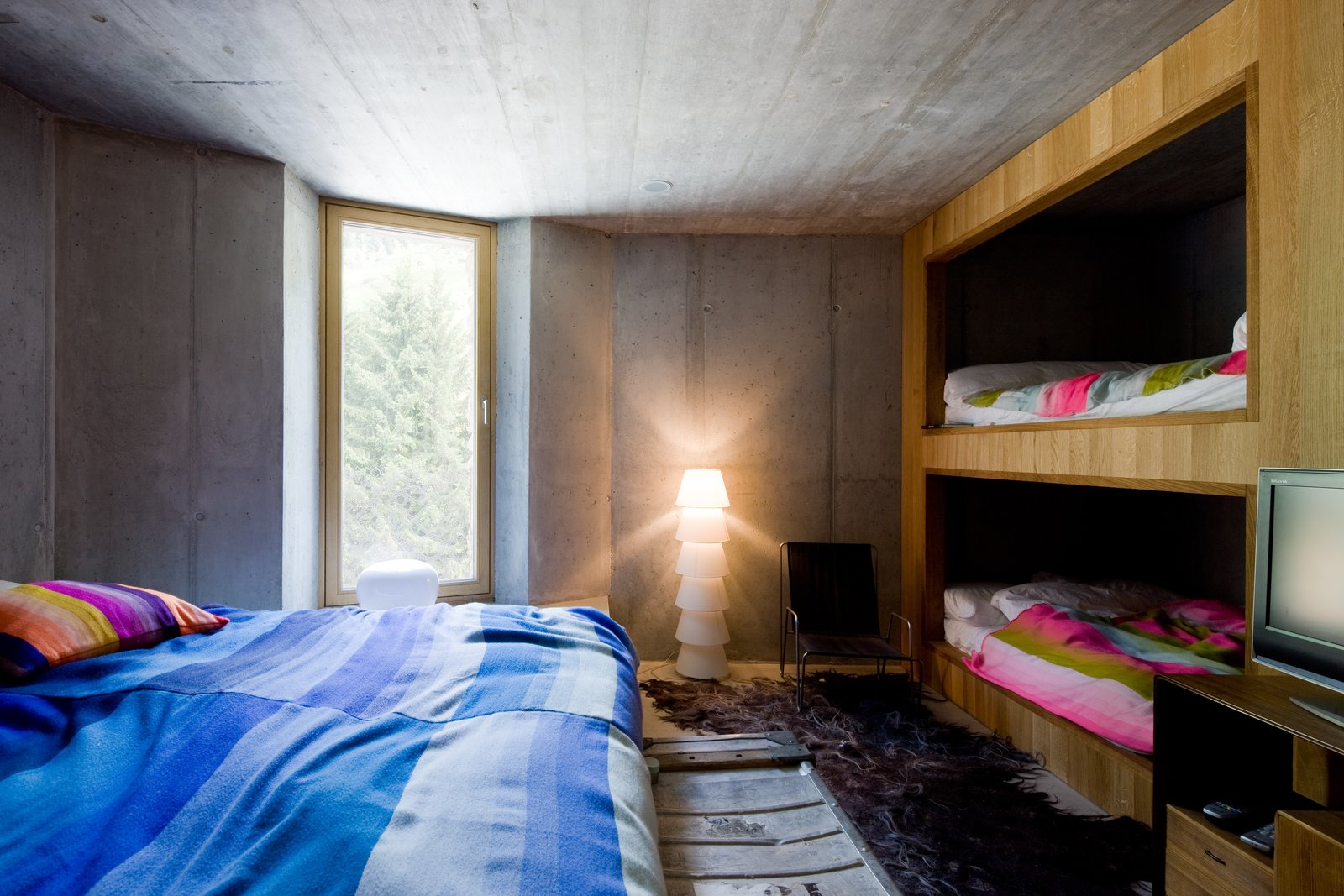 Tagged: Kids Room, Bed, Bunks, Bedroom, Teen Age, Pre-Teen Age, Neutral Gender, Chair, Lamps, and Rug Floor.  Photo 5 of 13 in Stay in a Swiss Vacation Home That's Literally Inside a Mountain