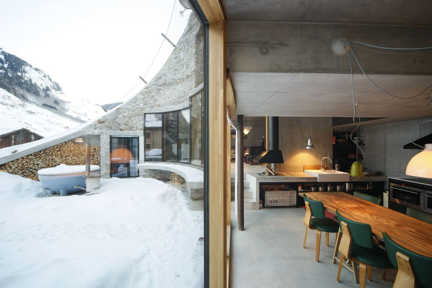 Tagged: Dining Room, Chair, Table, Wall Lighting, Concrete Floor, Pendant Lighting, and Hanging Fireplace.  Photo 6 of 13 in Stay in a Swiss Vacation Home That's Literally Inside a Mountain