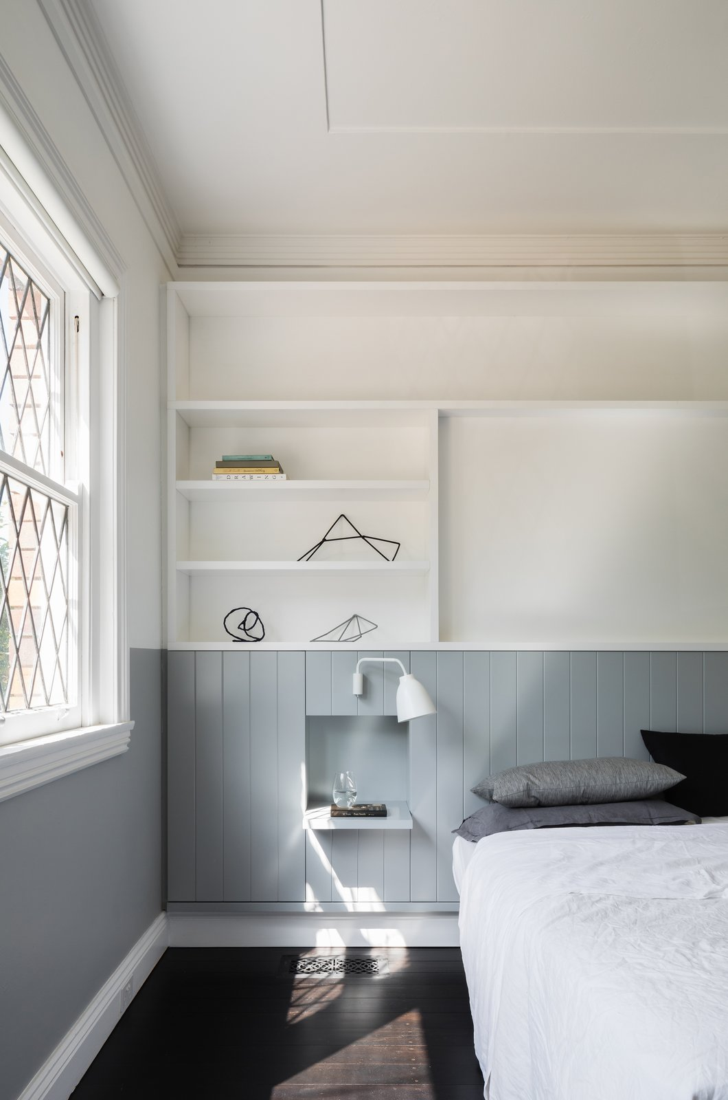 Tagged: Bedroom, Shelves, Wall Lighting, Bed, and Dark Hardwood Floor.  Photo 10 of 13 in This 1930s Bungalow in Sydney Was Preserved in the Front and Updated in the Back