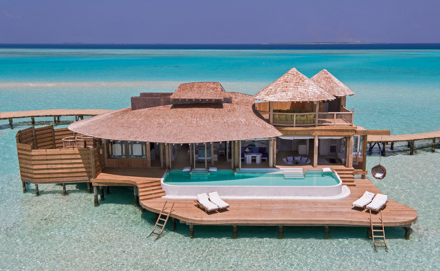 This resort is surrounded by 5.6 kilometers of private lagoon and includes villas with retractable roofs, private pools with catamaran nets and even waterslides.  Photo 2 of 9 in 9 Modern Maldivian Resorts With Spectacular Overwater Villas