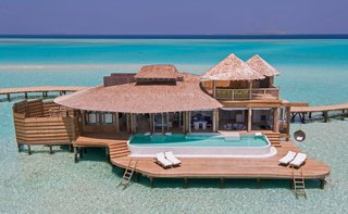 9 Modern Maldivian Resorts With Spectacular Overwater Villas - Photo 2 of 9 - This resort is surrounded by 3.5 miles of private lagoons and includes villas with retractable roofs, private pools with catamaran nets, and even waterslides.