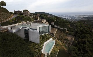 10 Cliffside Destinations That Will Make You Feel on Top of the World - Photo 4 of 10 - Located just outside of Barcelona and sited on a steep hill overlooking a valley and the Mediterranean Sea, X-House by Spanish architectural studio Cadaval & Sola-Morales has bold, fully-glazed angled frontages that look out to stunning views of the surrounding landscape.