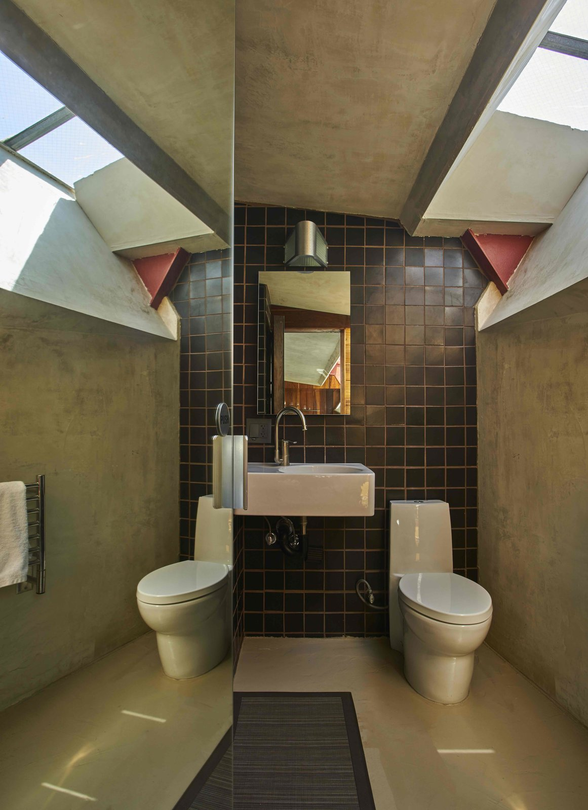 Tagged: Bath Room, Ceramic Tile Wall, Ceramic Tile Floor, Wall Lighting, Wall Mount Sink, and Two Piece Toilet.  Photo 11 of 13 in Escape to a John Lautner Micro-Resort in the Californian Desert