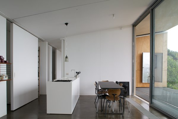 Modern home with kitchen, white cabinet, concrete floor, pendant lighting, cooktops, and drop in sink. Photo 6 of Sea View Villa