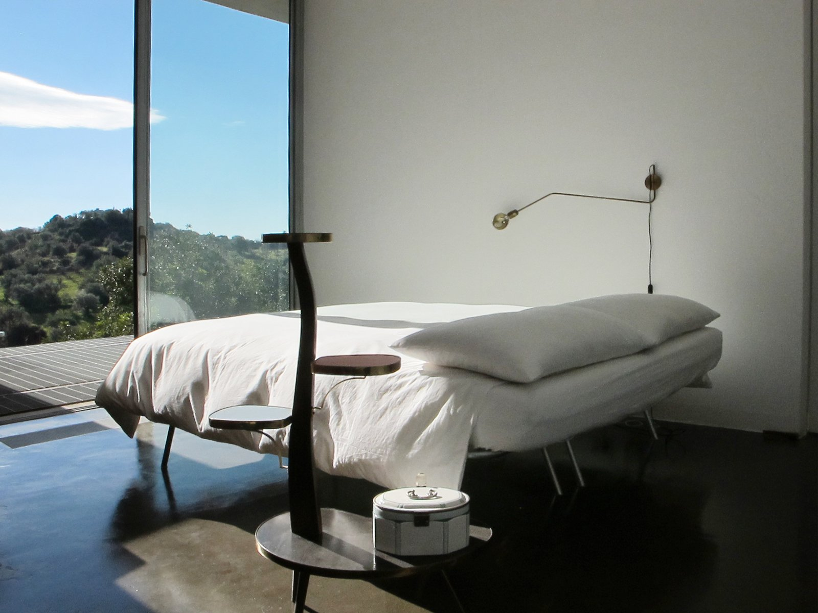 Tagged: Bedroom, Bed, Wall Lighting, Night Stands, and Concrete Floor.  Photo 9 of 12 in Stay in a Minimalist Villa in the Sicilian Countryside, Complete With Sea Views