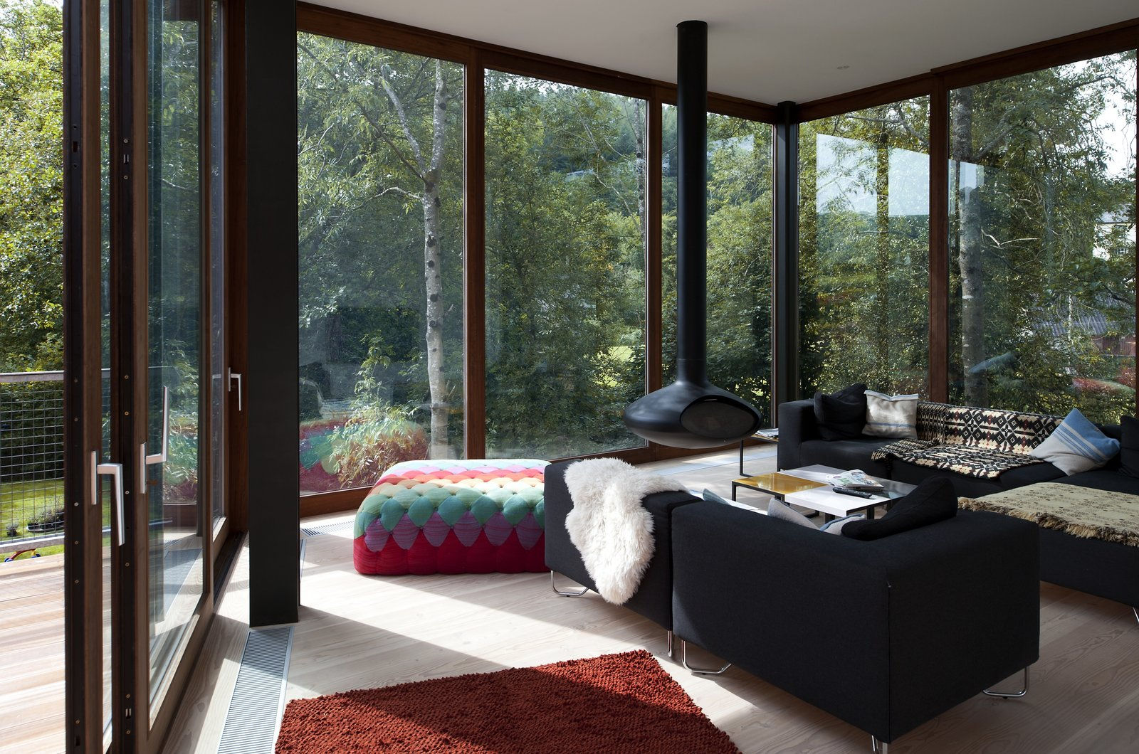 Tagged: Living Room, Sofa, Hanging Fireplace, Ottomans, and Light Hardwood Floor.  Ty Hedfan by Dwell from A Hovering House in the Welsh Hills That You Can Call Your Own For a Week