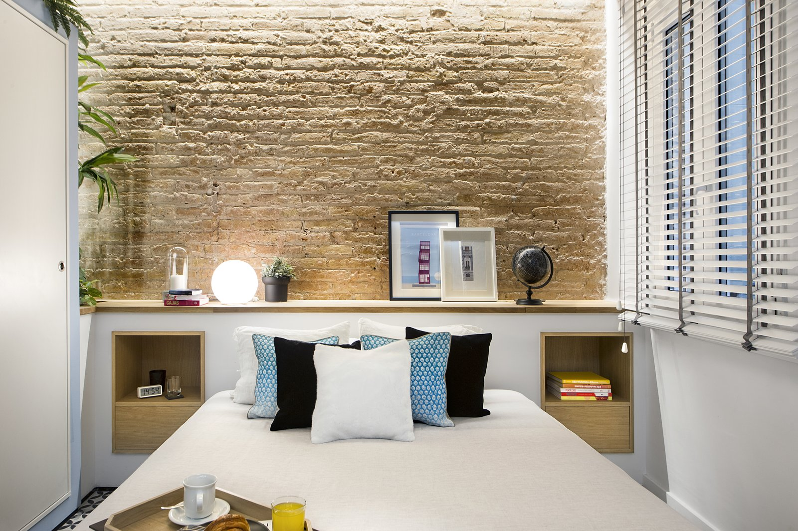 Tagged: Bedroom, Shelves, Table Lighting, Bed, and Porcelain Tile Floor. A Smart Layout Maximizes Space in This Compact Urban Beach Apartment in Barcelona - Photo 7 of 11