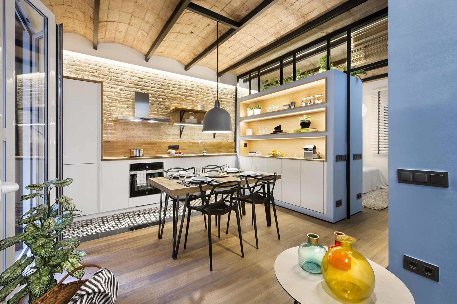 Tagged: Kitchen, Wood Counter, Light Hardwood Floor, Pendant Lighting, Wood Backsplashe, Wall Oven, Ceiling Lighting, Range Hood, Range, Drop In Sink, and Ceramic Tile Floor. A Smart Layout Maximizes Space in This Compact Urban Beach Apartment in Barcelona - Photo 9 of 11
