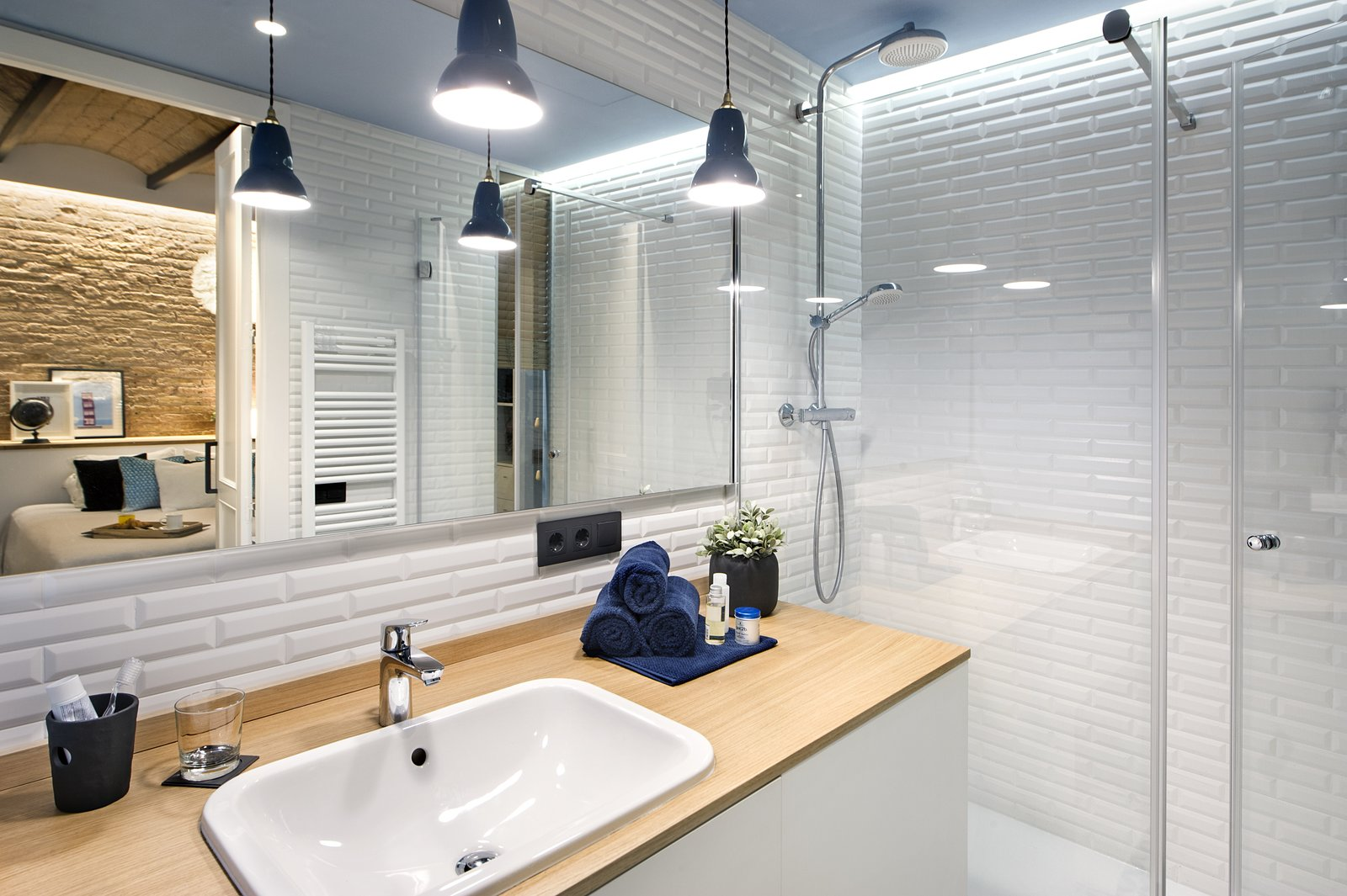 Tagged: Bath Room, Wood Counter, Enclosed Shower, Drop In Sink, Pendant Lighting, and Ceramic Tile Wall.  Photo 10 of 11 in A Smart Layout Maximizes Space in This Compact Urban Beach Apartment in Barcelona