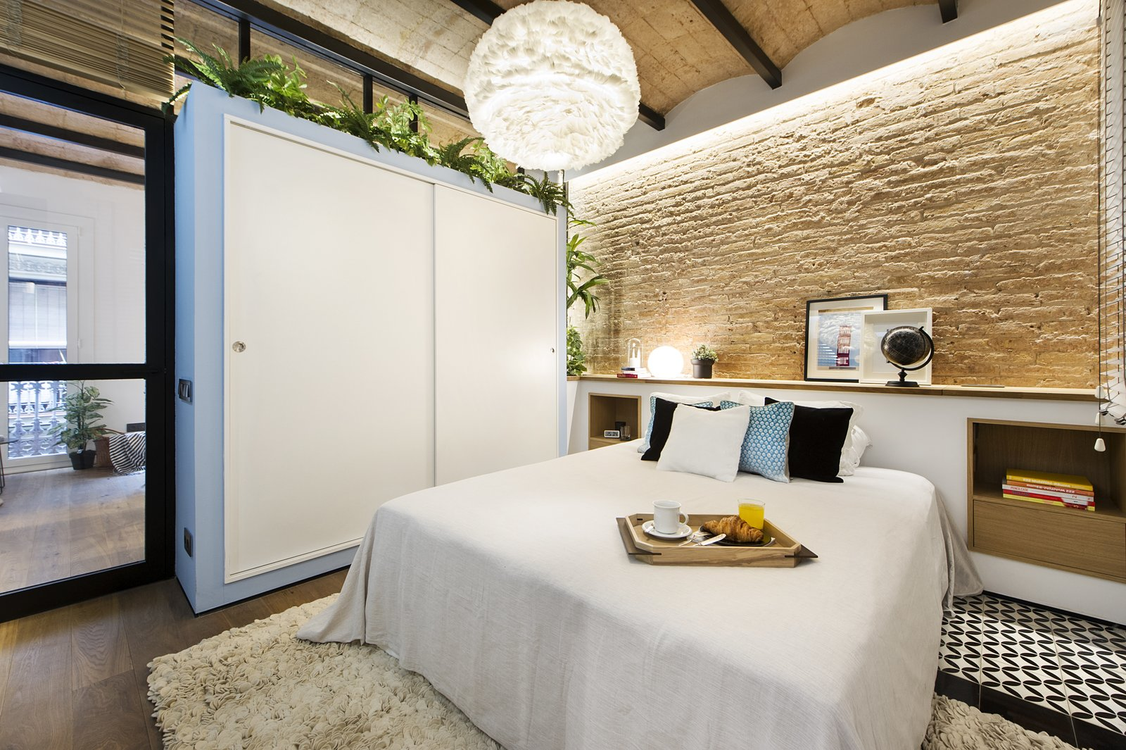 Tagged: Bedroom, Table Lighting, Bed, Storage, Pendant Lighting, Medium Hardwood Floor, and Ceramic Tile Floor.  Photo 6 of 11 in A Smart Layout Maximizes Space in This Compact Urban Beach Apartment in Barcelona