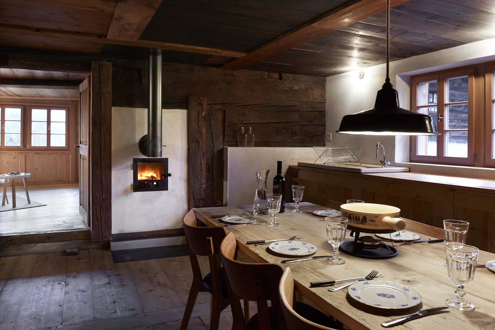 Tagged: Dining Room, Wood Burning Fireplace, Dark Hardwood Floor, Chair, Table, and Pendant Lighting. A Renovated Pagan House in the Swiss Alps Puts Guests in Touch With the Past - Photo 3 of 13