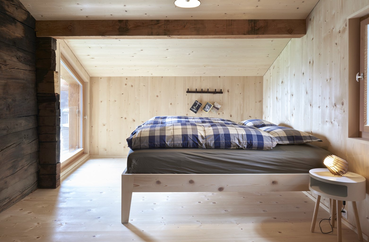 Tagged: Bedroom, Bed, Night Stands, Light Hardwood Floor, and Table Lighting.  Photo 5 of 13 in A Renovated Pagan House in the Swiss Alps Puts Guests in Touch With the Past