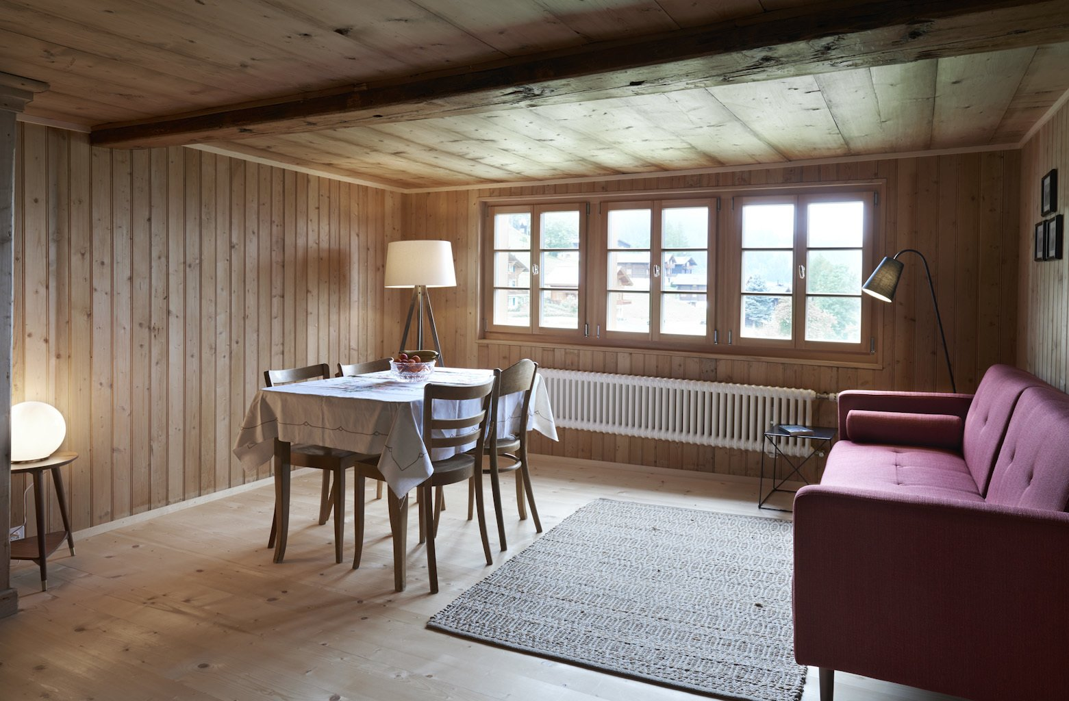 Tagged: Living Room, Sofa, Floor Lighting, Chair, Table, and Light Hardwood Floor.  Photo 6 of 13 in A Renovated Pagan House in the Swiss Alps Puts Guests in Touch With the Past