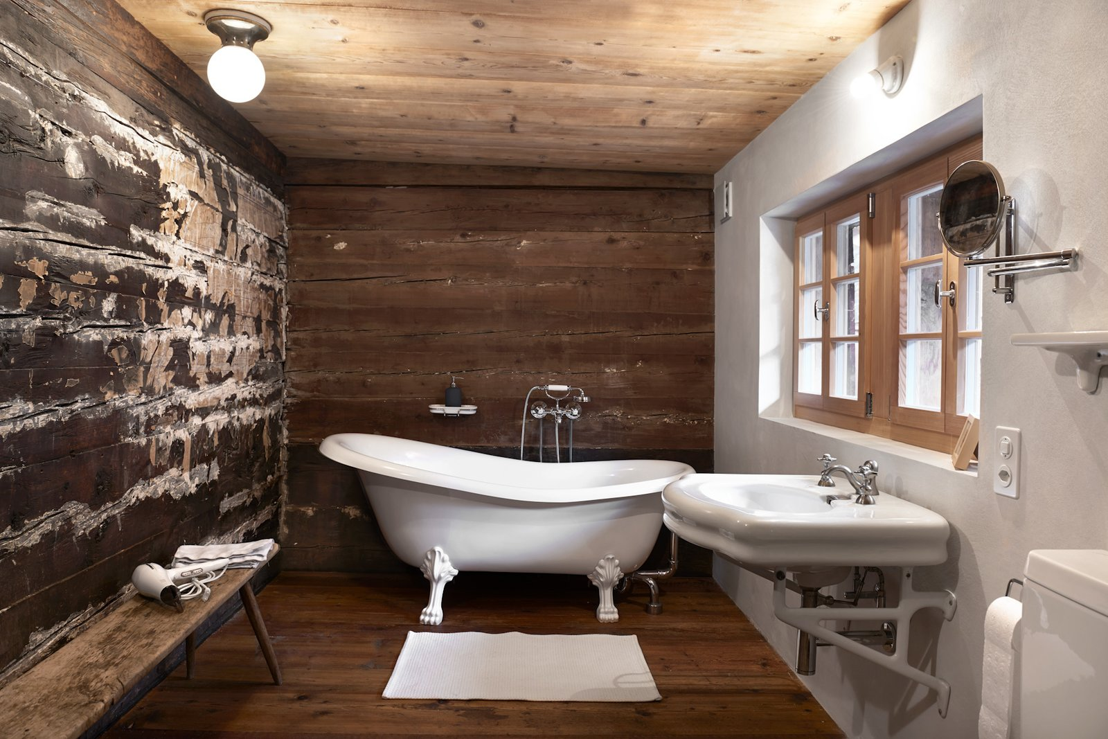 Tagged: Bath Room, Freestanding Tub, Wall Mount Sink, and Dark Hardwood Floor.  Photo 12 of 13 in A Renovated Pagan House in the Swiss Alps Puts Guests in Touch With the Past