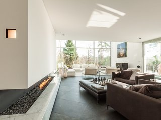 10 Modern Fireplaces That Make For Inviting Interiors - Photo 1 of 9 - This six-bedroom villa in Brussels has a cut-in-stone fireplace underneath a glass-enclosed walkway.