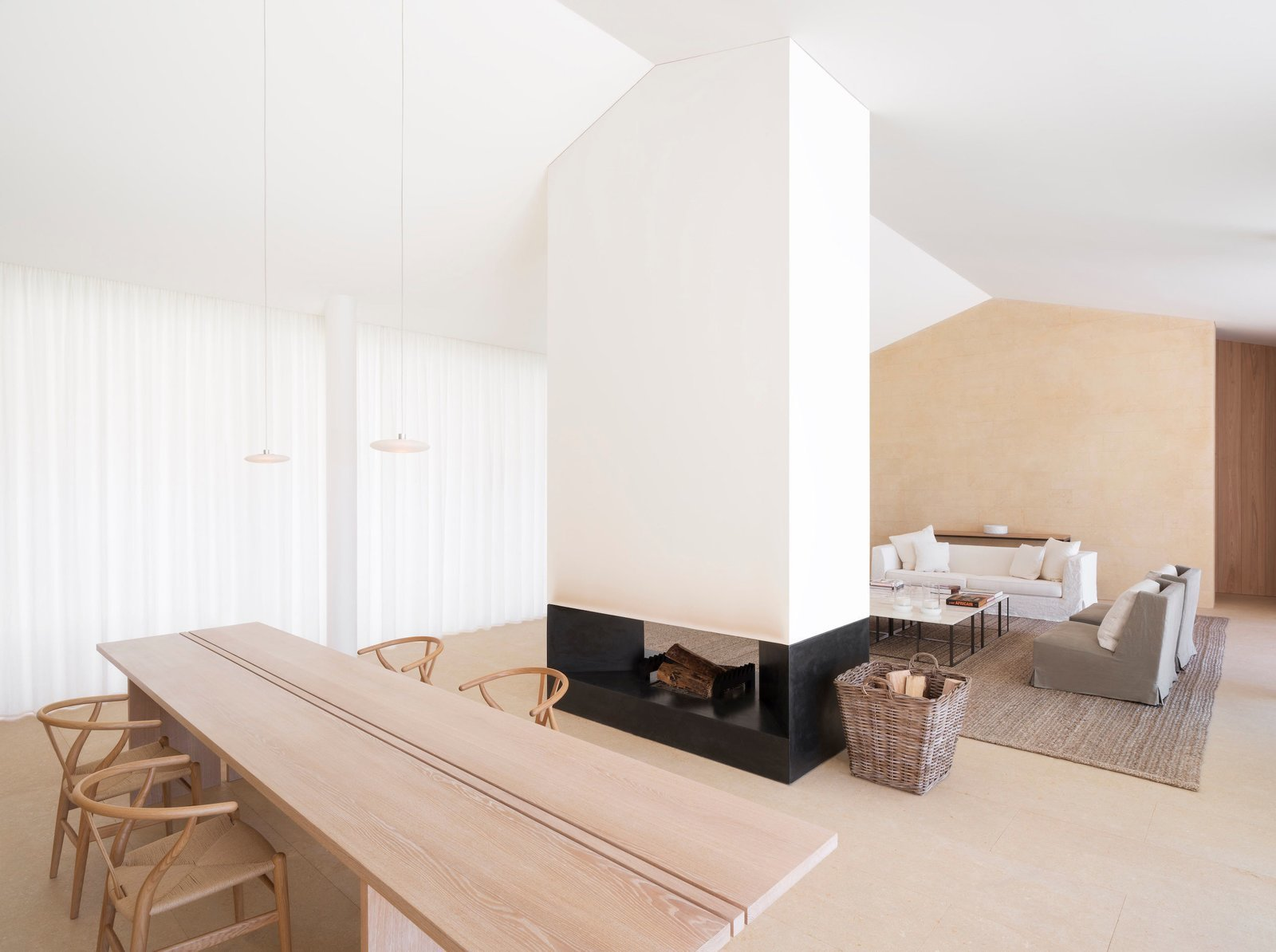 Designed by London architect John Pawson, this home in Saint Tropez has a freestanding fireplace framed by clean lines and bright white walls that acts as the heart a dynamic open-plan living room.