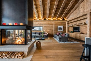 10 Modern Fireplaces That Make For Inviting Interiors - Photo 3 of 9 - A contemporary glass-encased fireplace in this Zermatt villa serves as a partition separating the living lounge from the dining area.