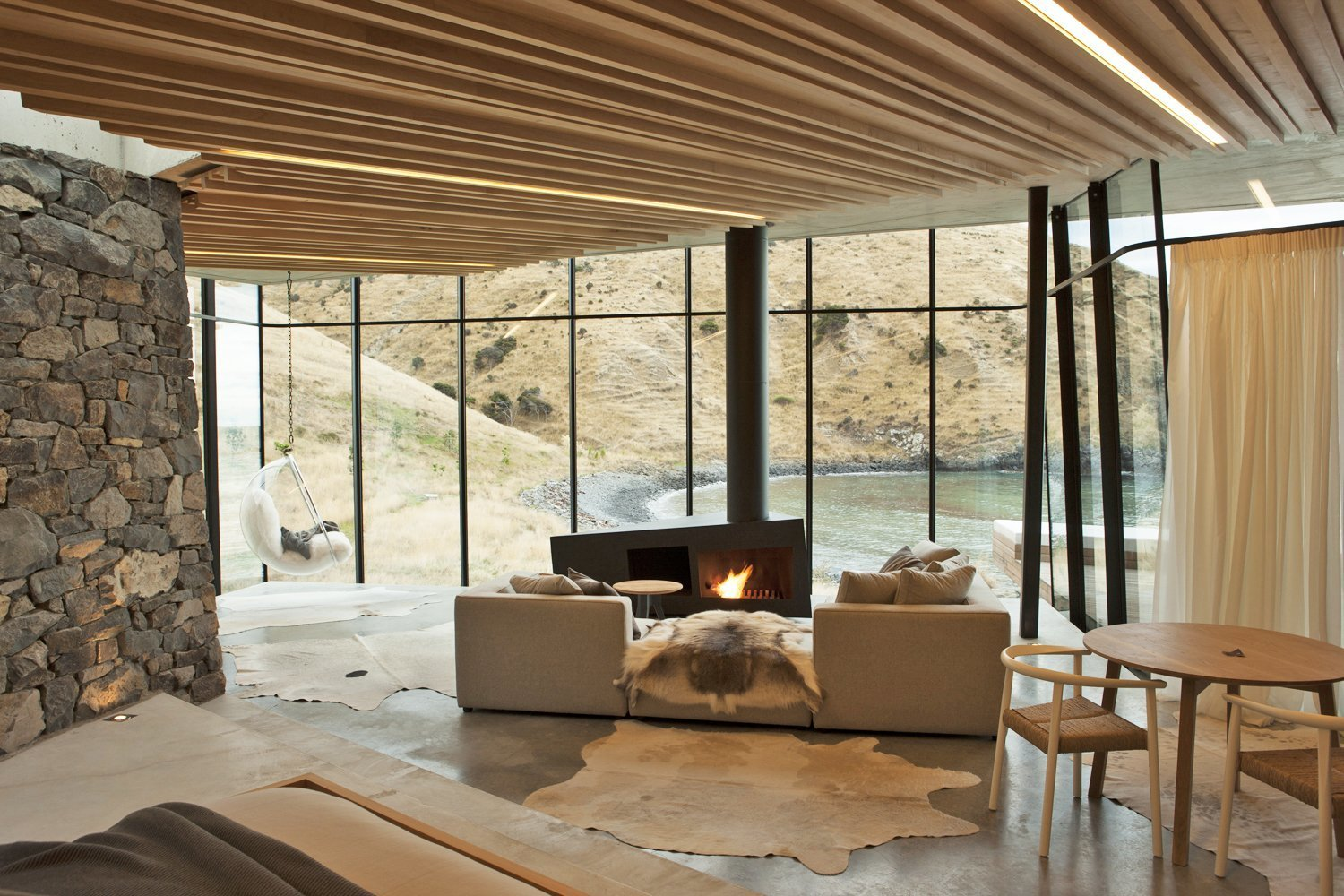 In this remote holiday rental home in New Zealand, guests can warm themselves by the asymmetrically shaped fireplace while looking out to views of a gorgeous, deserted by.  Photo 6 of 10 in 10 Modern Fireplaces That Make For Inviting Interiors
