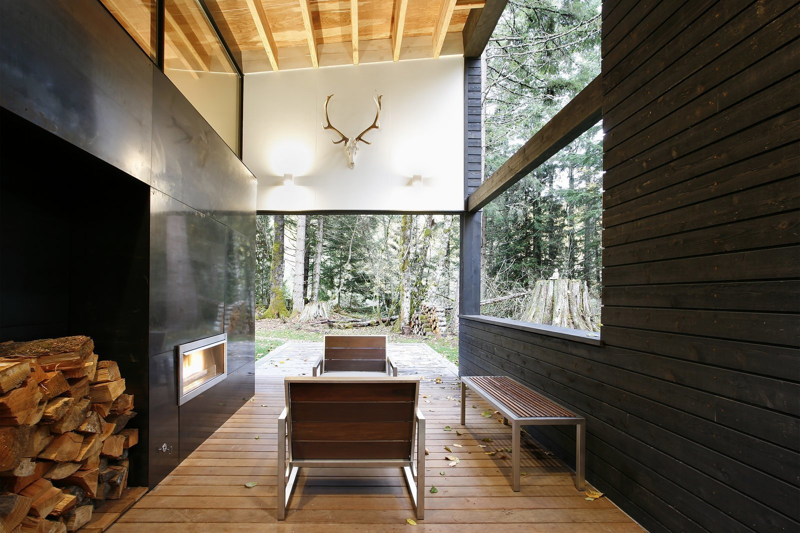 In Greenwater, Washington, a courtyard house on a river was designed with a steel-clad fireplace mass that separates the living room from a covered outdoor patio.