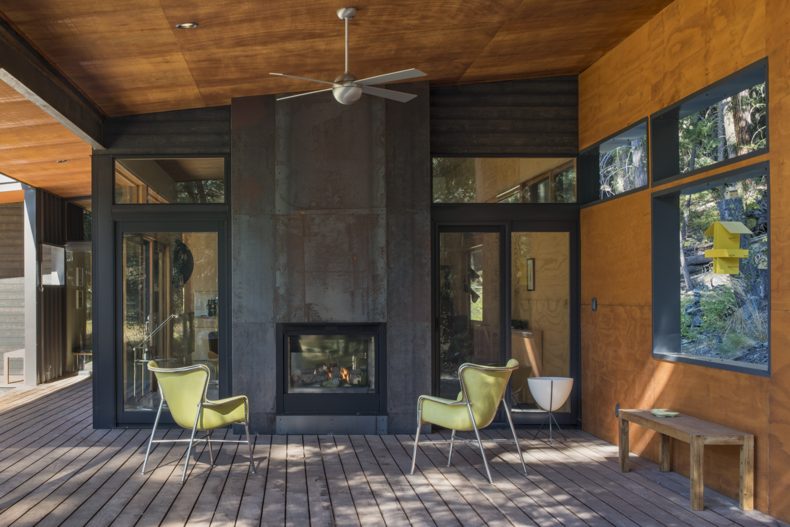 A modern cabin in Washington's Methow Valley has a fireplace with glazing on to opposite sides, so its owners can watch the embers of the fireplace glowing from both indoors and out on the patio.