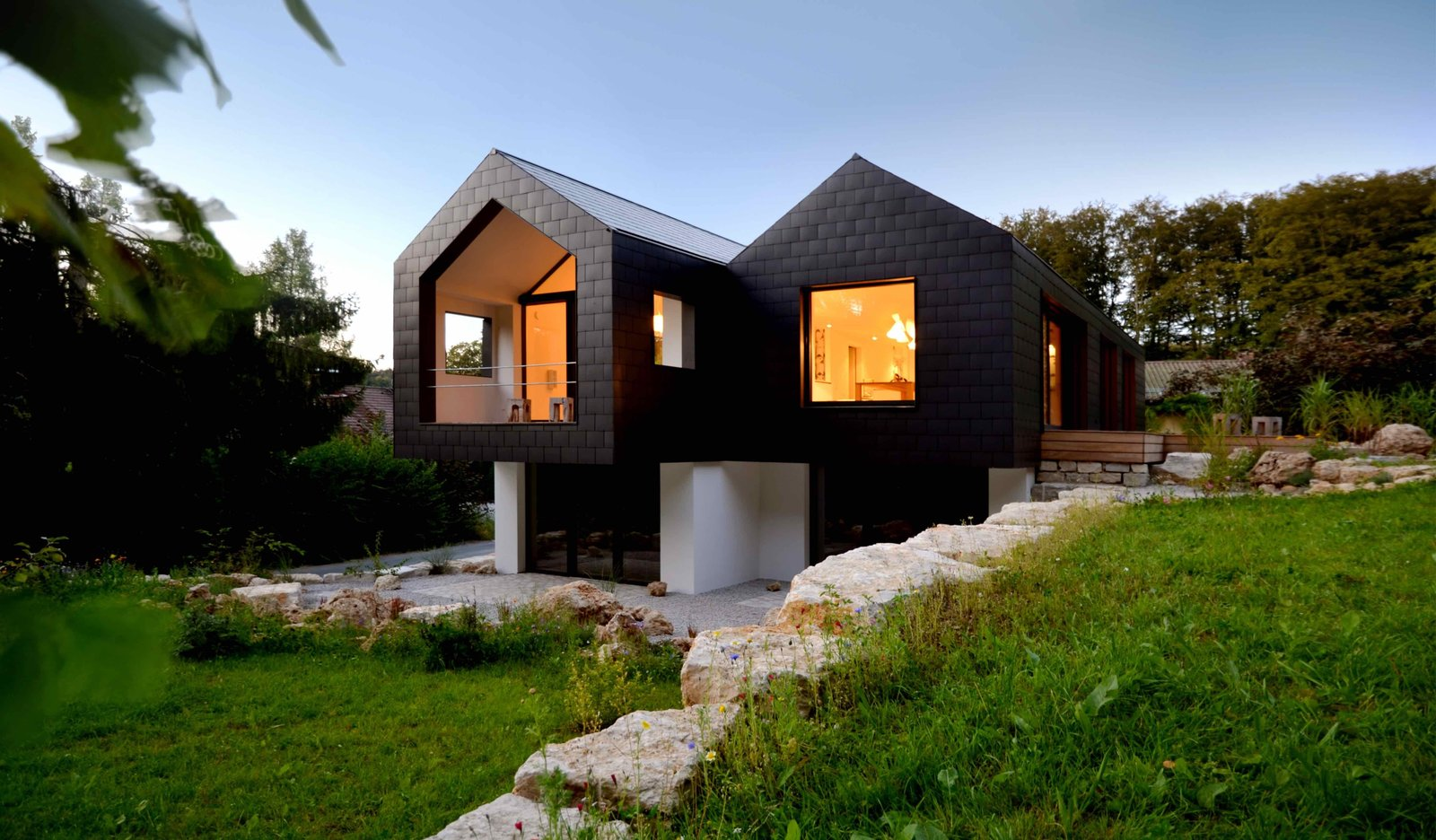 Tagged: Outdoor, Front Yard, Trees, Stone Patio, Porch, Deck, Boulders, and Grass.  Refugium Betzenstein by Dwell from Escape to a Bio-Passive Vacation Refuge in a Bavarian Nature Park