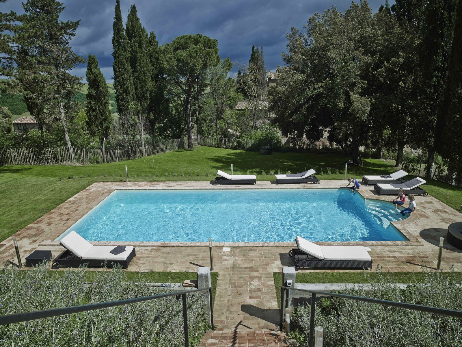 Tagged: Outdoor, Back Yard, Grass, Swimming Pools, Tubs, Shower, Large Pools, Tubs, Shower, Vertical Fences, Wall, and Trees.  Photo 3 of 11 in Stay in a Modern, Industrial Home That's Hidden Inside a Traditional Tuscan Villa