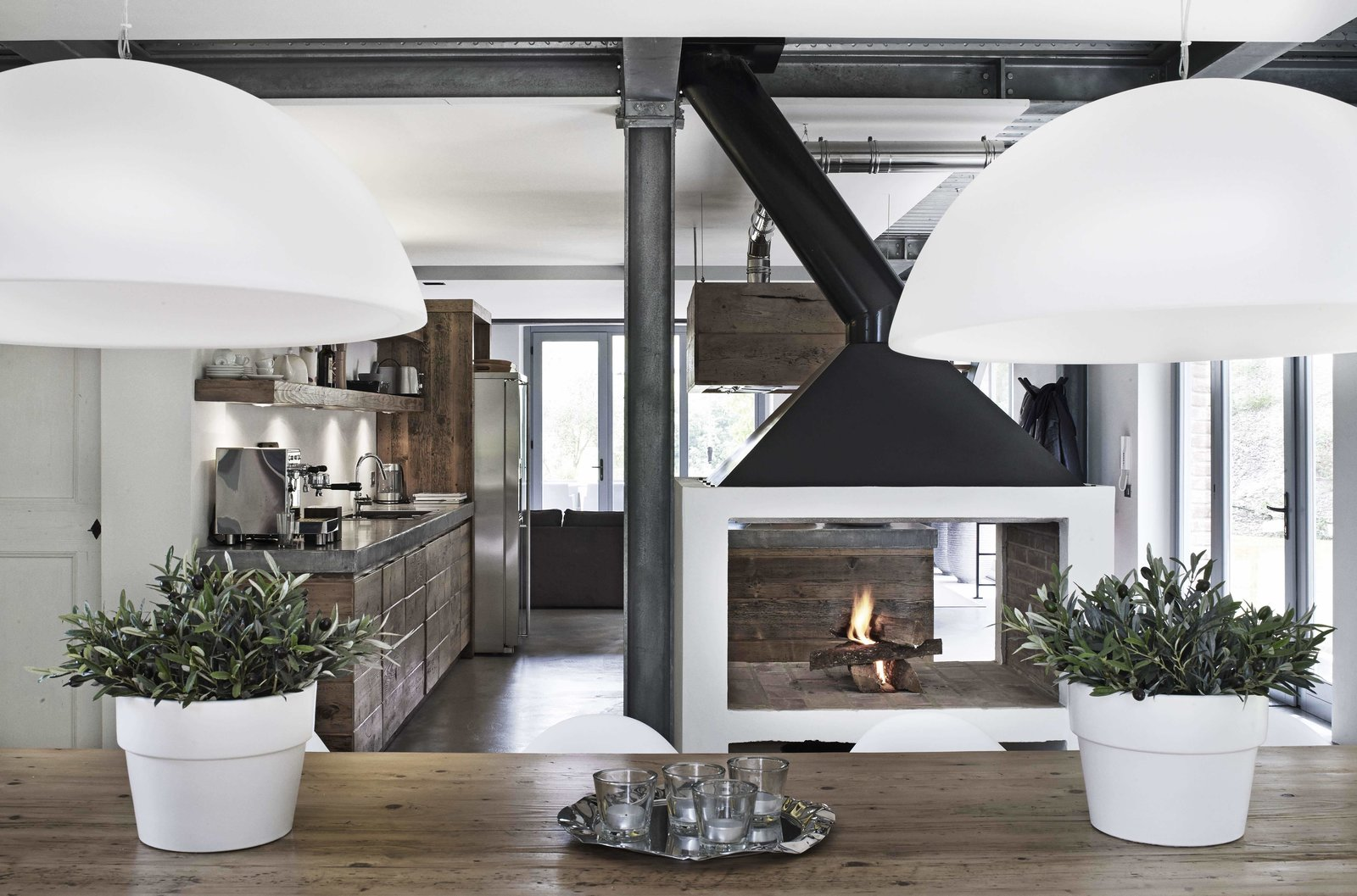 Tagged: Dining Room, Pendant Lighting, Standard Layout Fireplace, Two-Sided Fireplace, Dark Hardwood Floor, and Wood Burning Fireplace.  Photo 4 of 11 in Stay in a Modern, Industrial Home That's Hidden Inside a Traditional Tuscan Villa