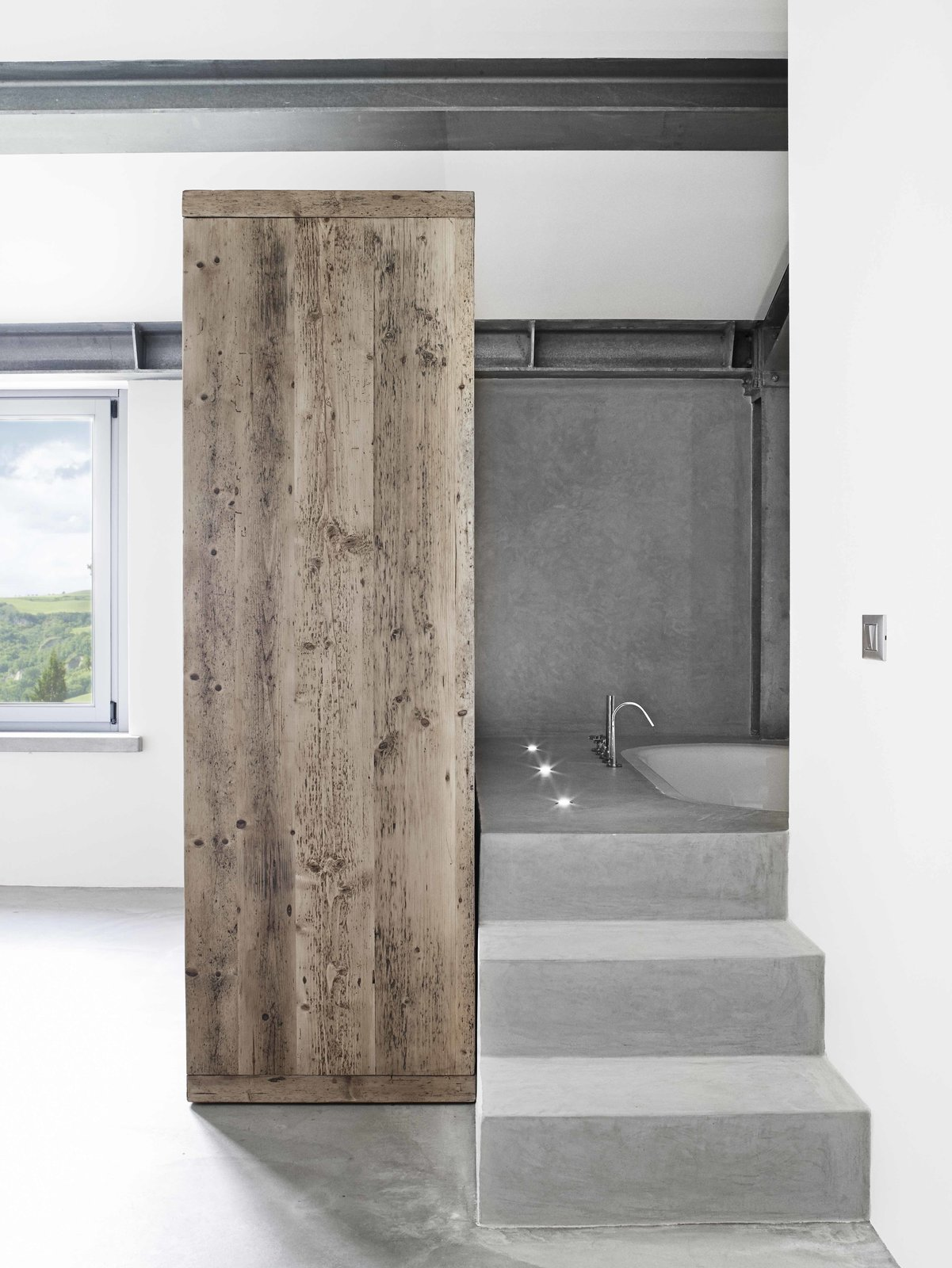 Tagged: Bath Room, Undermount Tub, Soaking Tub, and Concrete Floor. Stay in a Modern, Industrial Home That's Hidden Inside a Traditional Tuscan Villa - Photo 10 of 11