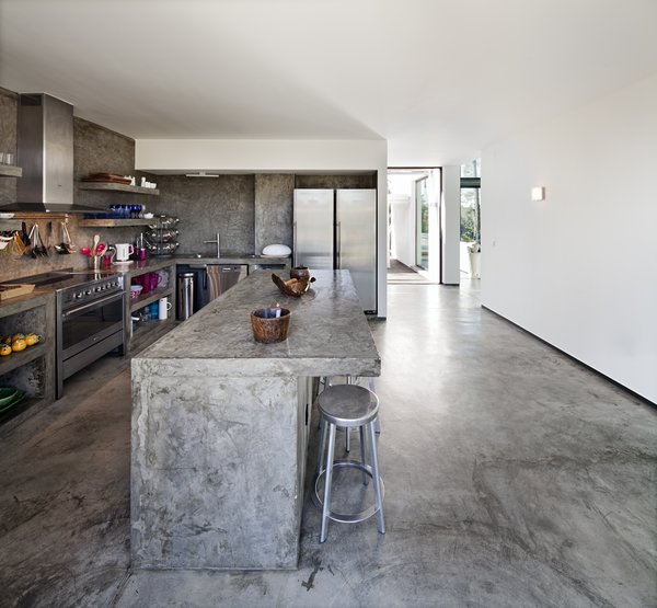 Modern home with kitchen, concrete counter, dishwasher, range, range hood, wall oven, refrigerator, and drop in sink. Photo 13 of Villa Caetana