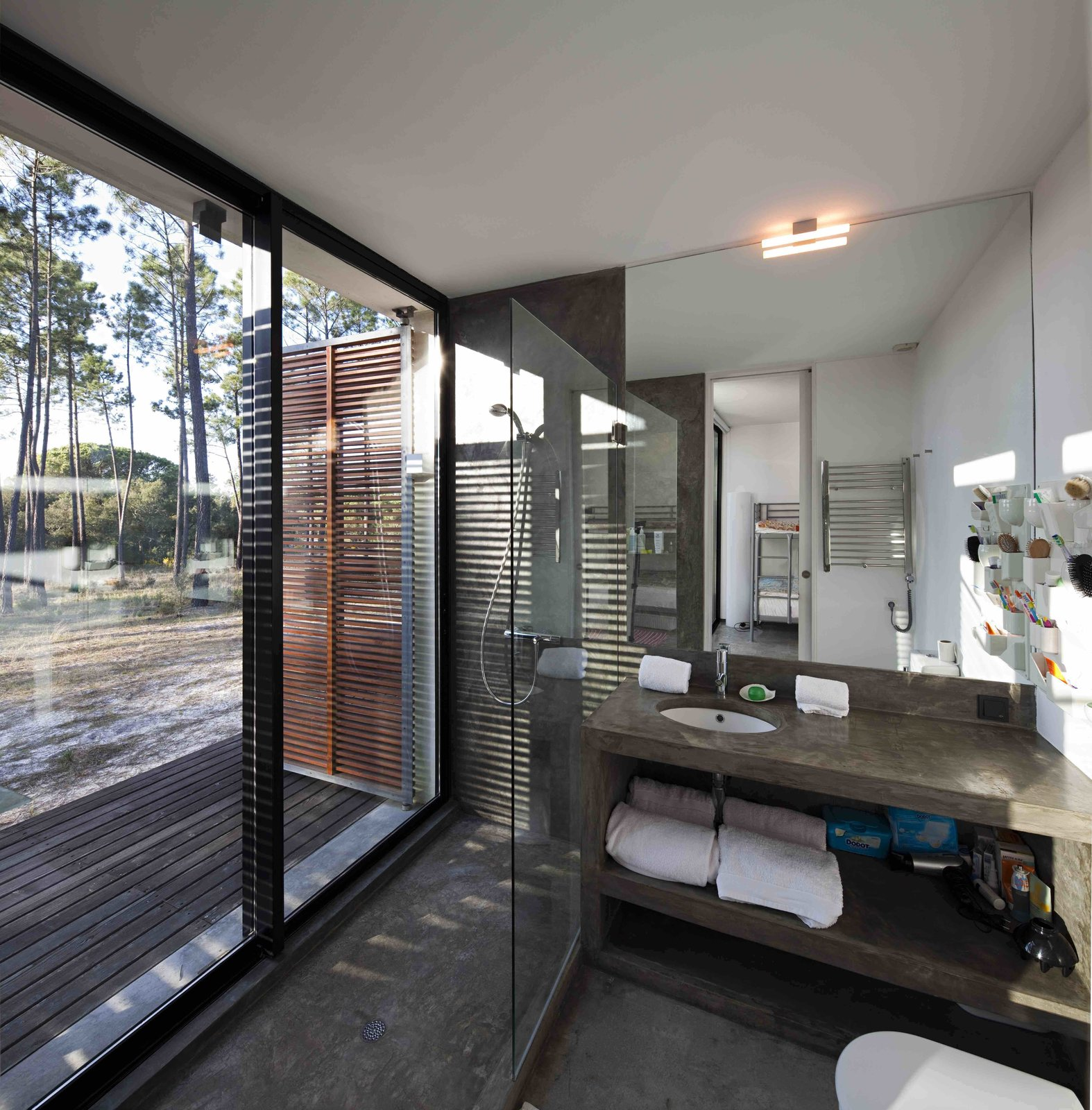 Tagged: Bath Room, Concrete Counter, Concrete Floor, Open Shower, Drop In Sink, and Wall Lighting.  Photo 7 of 15 in Escape to a Light-Filled, Beach-Meets-Forest Retreat in Portugal