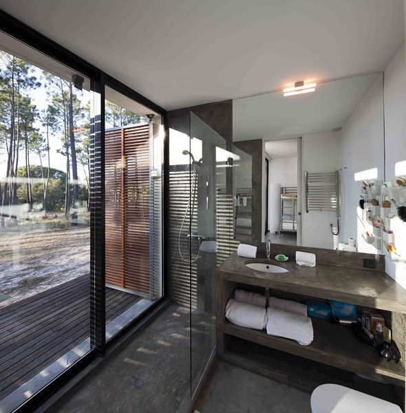 Modern home with bath room, concrete counter, concrete floor, open shower, drop in sink, and wall lighting. Photo 7 of Villa Caetana