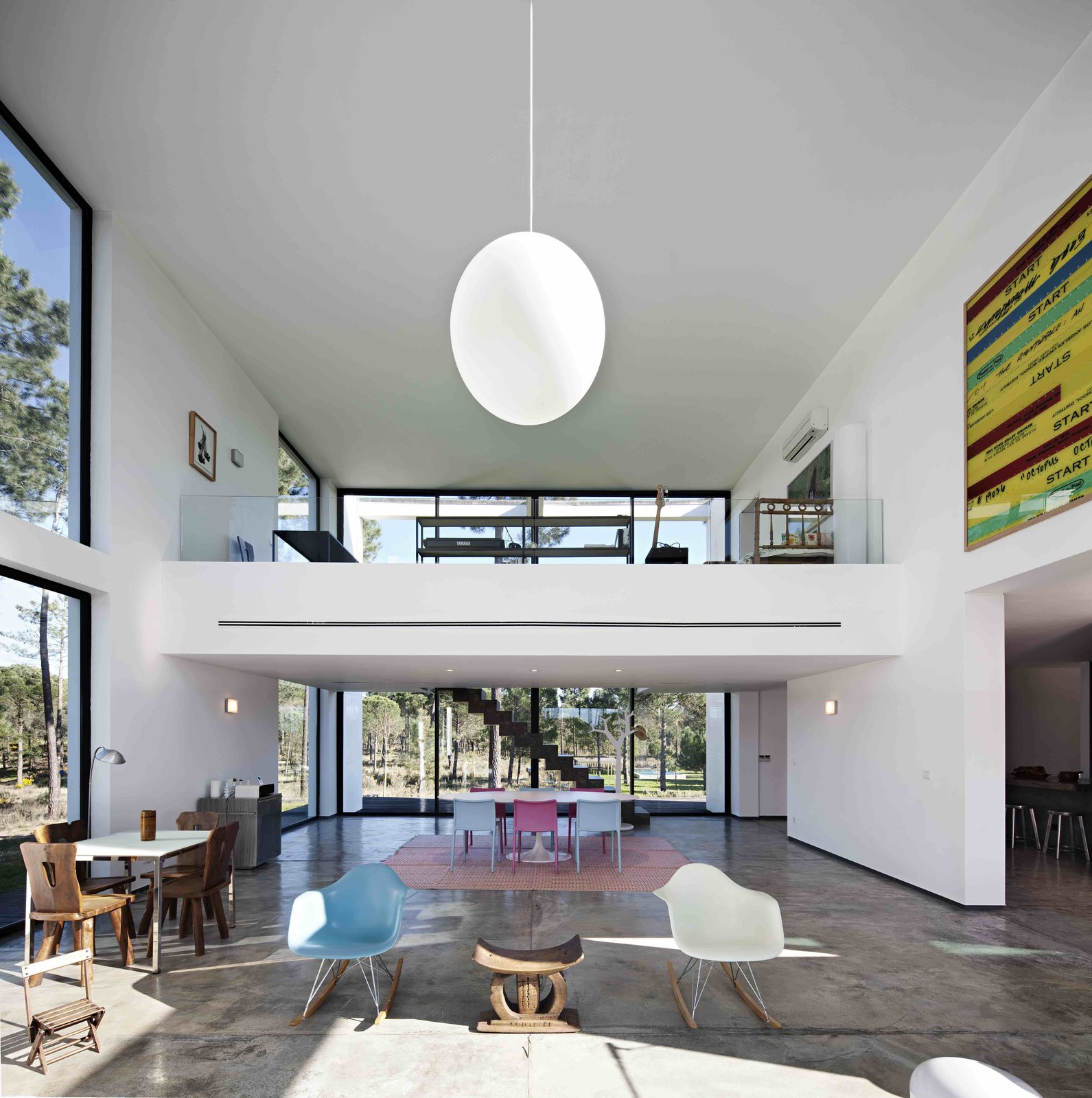 Tagged: Living Room, Table, Stools, Lamps, Chair, Table Lighting, Concrete Floor, and Pendant Lighting.  Photo 2 of 15 in Escape to a Light-Filled, Beach-Meets-Forest Retreat in Portugal