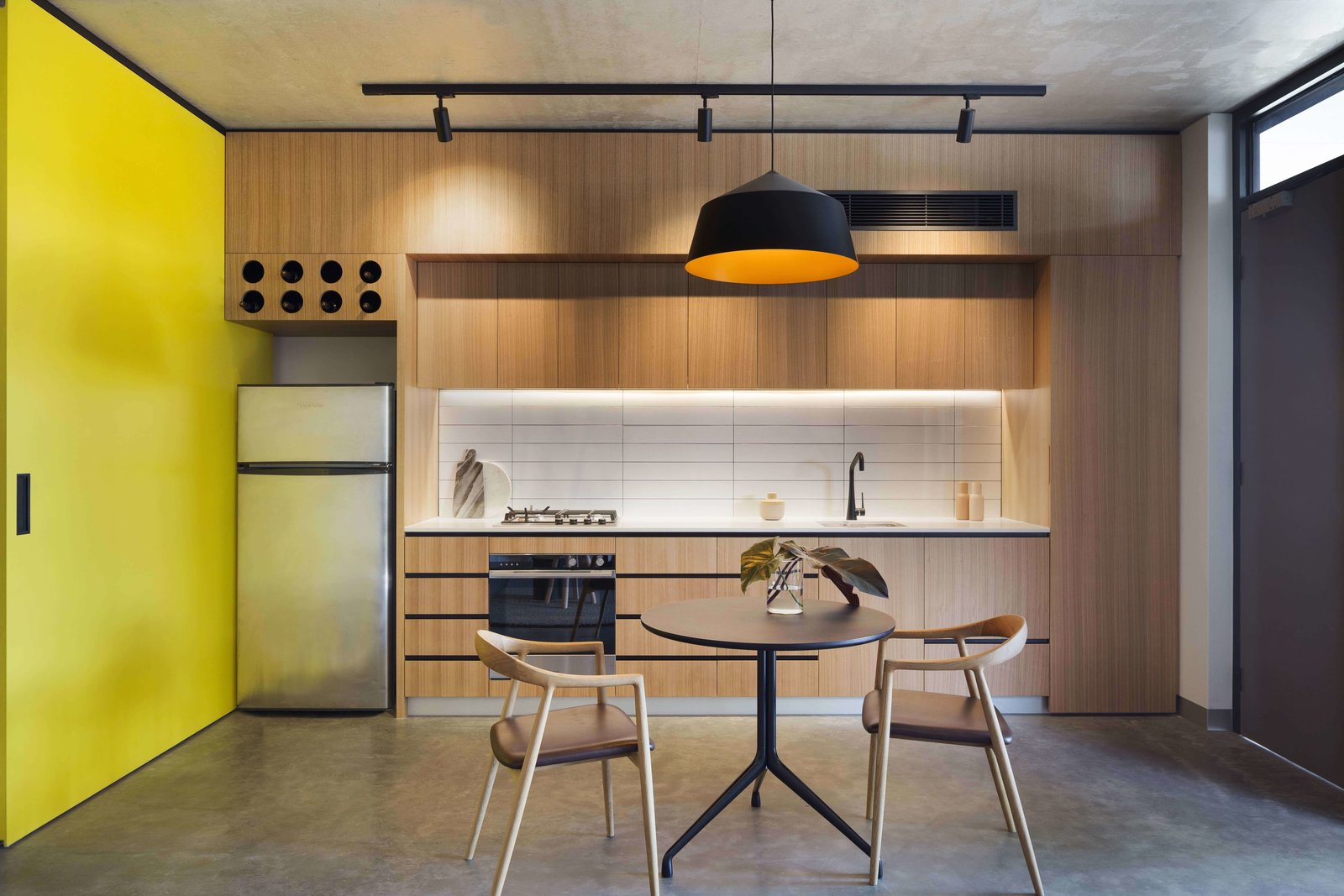 Tagged: Kitchen, Wood Cabinet, Ceramic Tile Backsplashe, Pendant Lighting, Refrigerator, Wall Oven, Concrete Floor, Drop In Sink, and Cooktops.  Photo 11 of 14 in What Looks Like a Single Dwelling in Melbourne Actually Holds Six Walk-Up Apartments