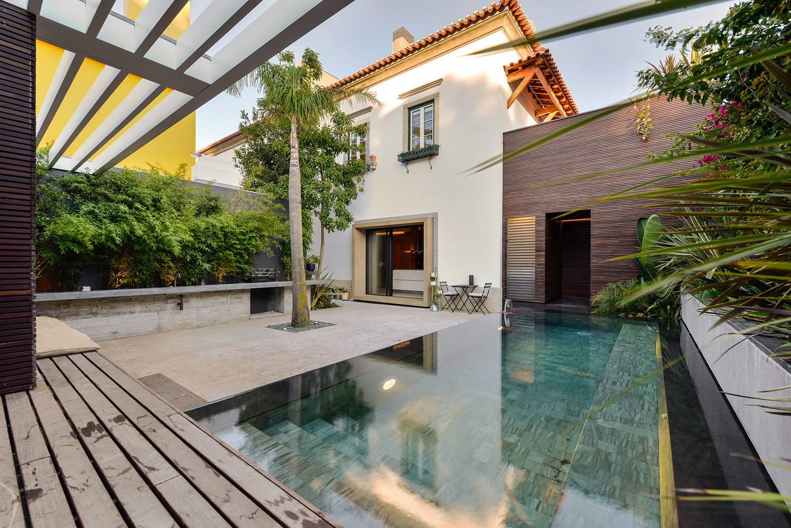 Tagged: Outdoor, Small Pools, Tubs, Shower, Back Yard, Trees, Decking Patio, Porch, Deck, Gardens, Infinity Pools, Tubs, Shower, and Swimming Pools, Tubs, Shower.  Photo 6 of 16 in An Architect Renovates His 1920s Home in Portugal, While Preserving the Exterior Shell