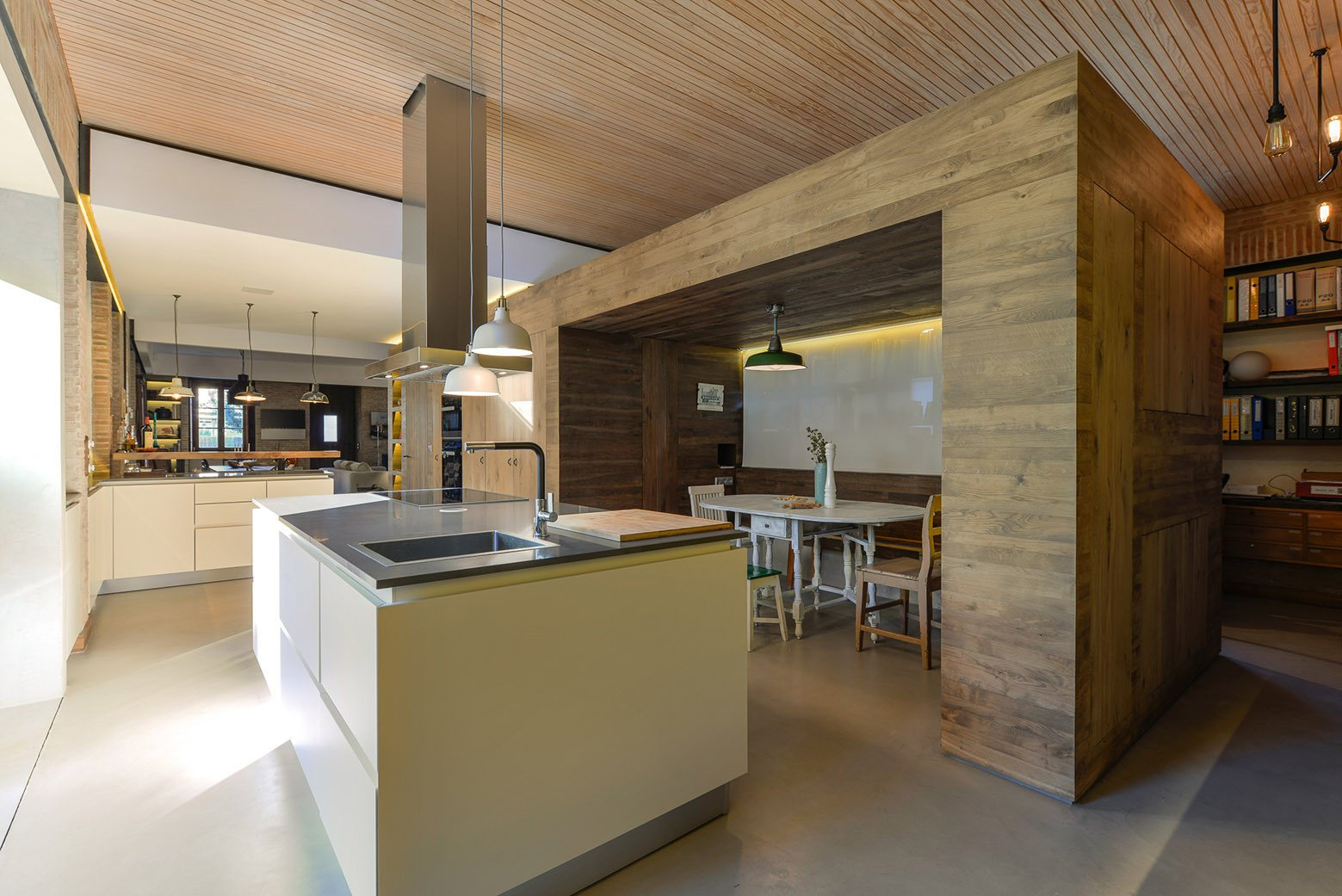 Tagged: Kitchen, Metal Counter, White Cabinet, Concrete Floor, Pendant Lighting, Cooktops, Drop In Sink, and Range Hood.  Photo 10 of 16 in An Architect Renovates His 1920s Home in Portugal, While Preserving the Exterior Shell