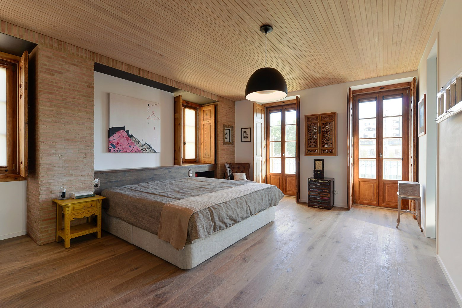 Tagged: Bedroom, Pendant Lighting, Bed, Chair, Night Stands, and Light Hardwood Floor.  Photo 11 of 16 in An Architect Renovates His 1920s Home in Portugal, While Preserving the Exterior Shell