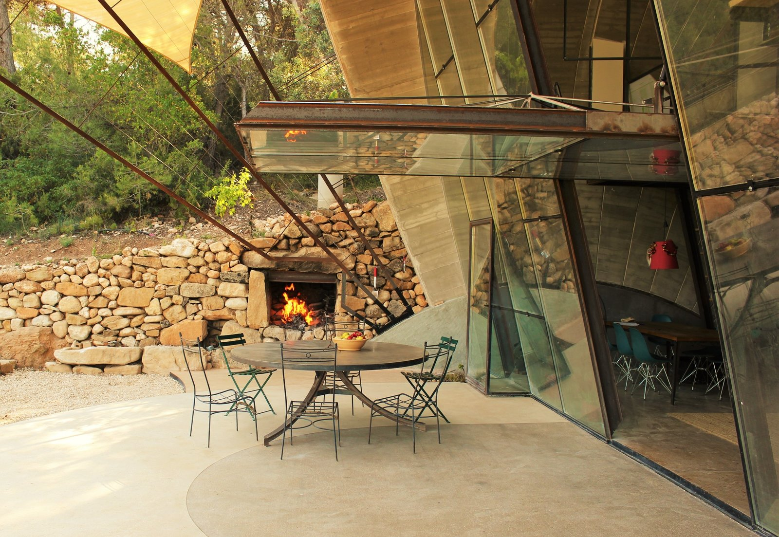 Tagged: Chair, Table, Outdoor, Small Patio, Porch, Deck, Front Yard, Boulders, and Trees.  Photo 4 of 8 in Stay in a Domed, Glass-Front Vacation Home in a Spanish Forest